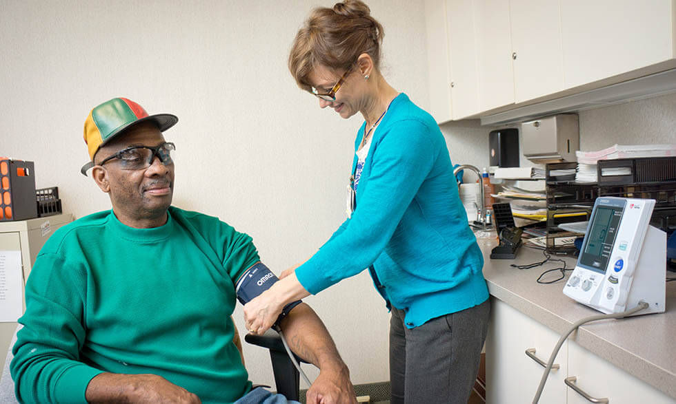 NIH clinical trial participant Curtis Minor has his blood pressure taken by Miriam Baird, R.N.