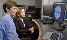 National Institute of Mental Health researcher David Jangraw, Ph.D. (left), reviews brain scans with Renée Fleming at NIH.
