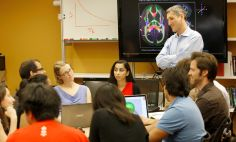 Daniel Reich, M.D., Ph.D. (standing) listens to team members at NIH.