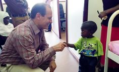 Russell E. Ware M.D., Ph.D., meets with a young sickle cell patient in Africa.