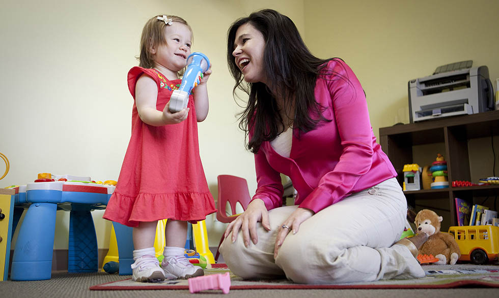 Karen Pierce, Ph.D., plays with a toddler referred to her program by a local pediatrician.